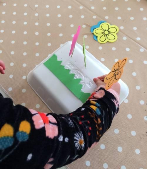 Bambina che crea una prato con fiorellini fatti con post-it